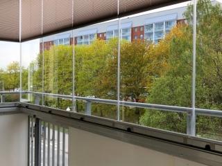 Inglasad balkong med vit dekorvägg och plisségardiner - NIKA Inglasning