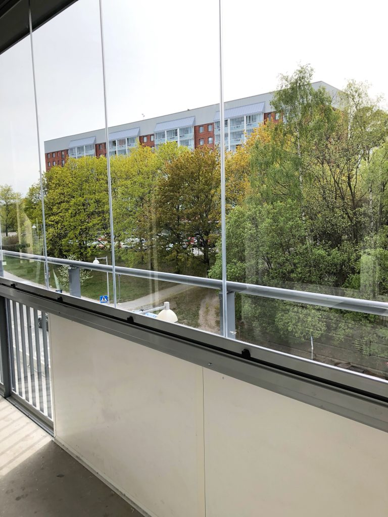 Ramfri balkonginglasning med högblank vit dekorvägg och en separat sektion med glas på räcket